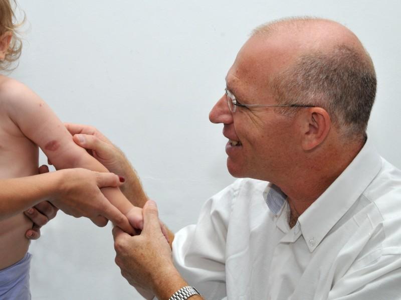 """ד""""ר דוד לשם בודק מטופל במסגרת השירות לכירורגיה פלסטית בילדים"""